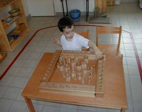 Montessori student playing with various weights.