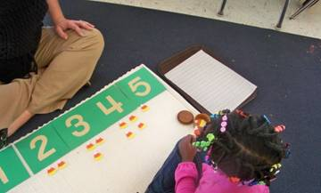 Montessori student playing a number-game with a teacher.